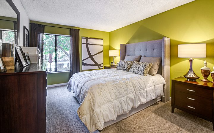 Furnished bedroom with ample natural light from window at Woodland Hills apartments community Alura