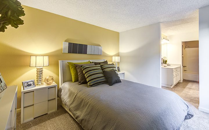 Brightly lit furnished bedroom next to open bathroom at Woodland Hills apartments community Alura