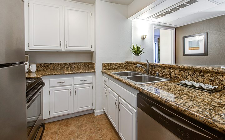 Kitchen with brown stone counter and white cabinets at Woodland Hills apartments community Alura