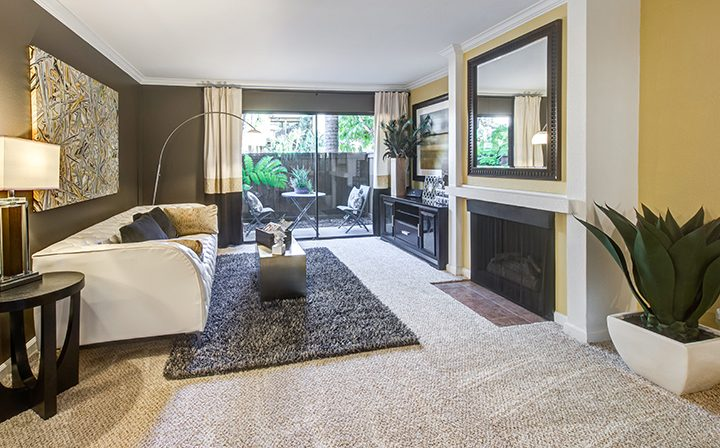 Furnished living room with fireplace and glass door to patio at Alura, Woodland Hills apartments