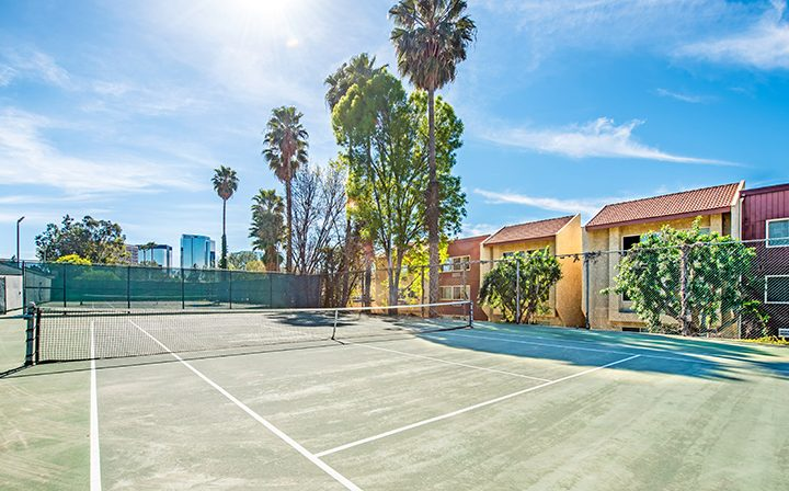 Outdoor tennis courts on a sunny day next to palm trees at Woodland Hills apartments community Alura
