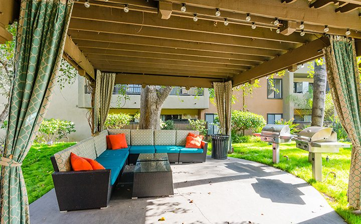 Sectional couch outdoors in shade beneath gazebo with BBQ grills at Woodland Hills apartments Alura