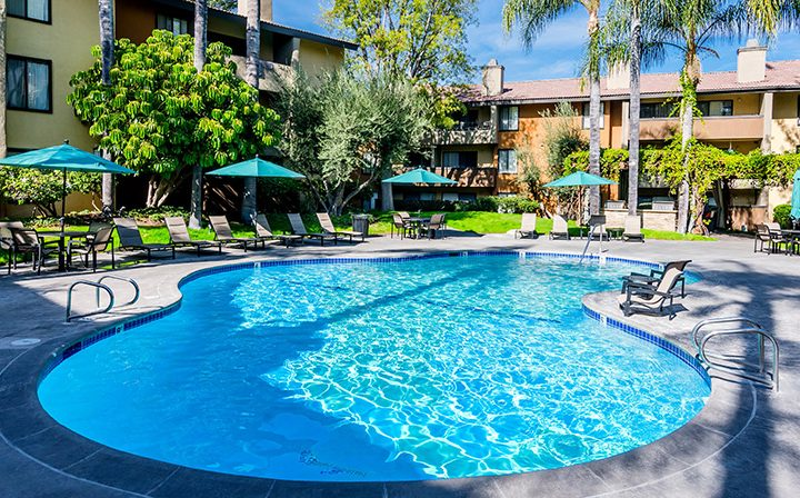 Resort-style pool with chairs and teal umbrellas at Woodland Hills apartments community Alura