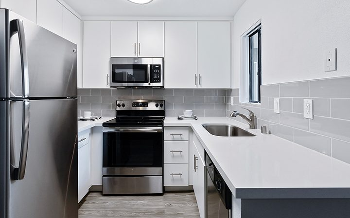 White renovated kitchen with range and dishwasher at Woodland Hills apartments community Alura
