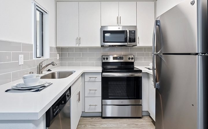 Renovated kitchen with white counters and tile wall at Woodland Hills apartments community Alura