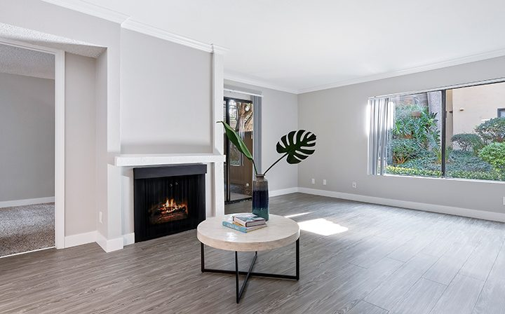 Renovated living room with fireplace and large windows at Woodland Hills apartments community Alura