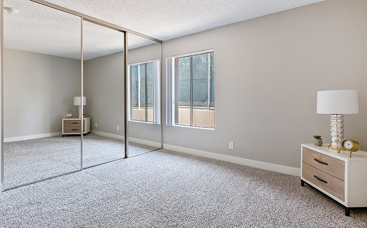Mirrored closet doors in large renovated bedroom at Woodland Hills apartments community Alura