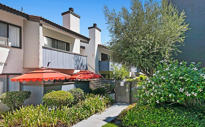 Exterior view of units and verdant path at Alura, a Woodland Hills apartments community