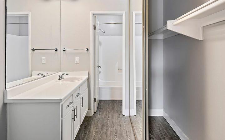 Bathroom sink and mirrored closet at Woodland Hills apartments community Alura
