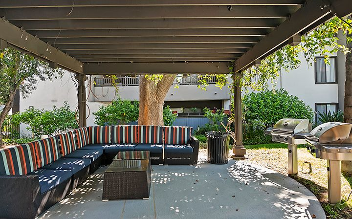 Cabana with padded chairs next to BBQ at Alura, a Woodland Hills apartments community