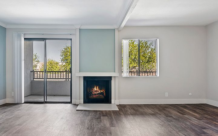 Unfurnished living room with fireplace and balcony exit at Woodland Hills apartments community Alura