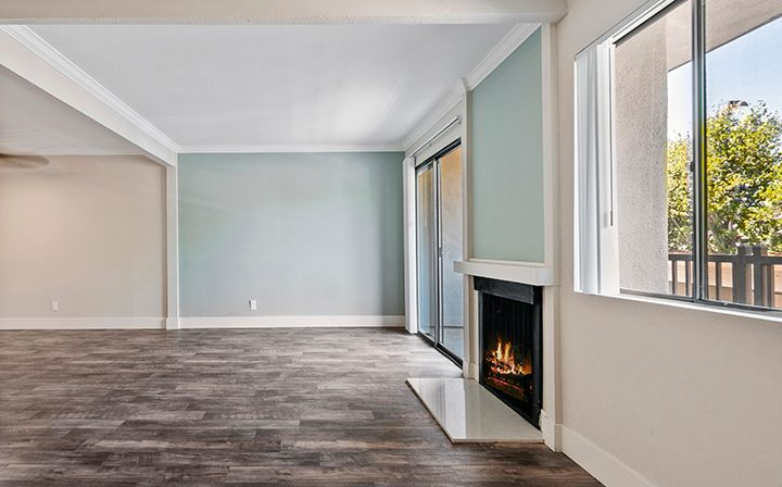 Unfurnished living room with fireplace and window at Woodland Hills apartments community Alura