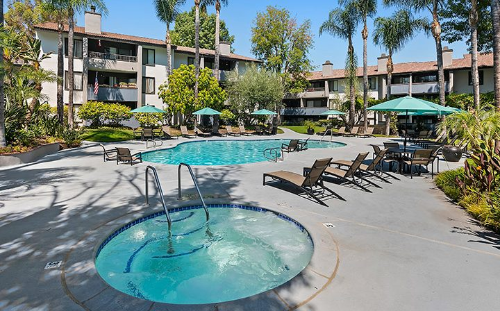 Hot tub spa next to chairs and teal umbrellas at Woodland Hills apartments community Alura