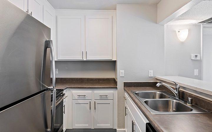 White renovated kitchen with range and dishwasher at Woodland Hills apartments community Alura