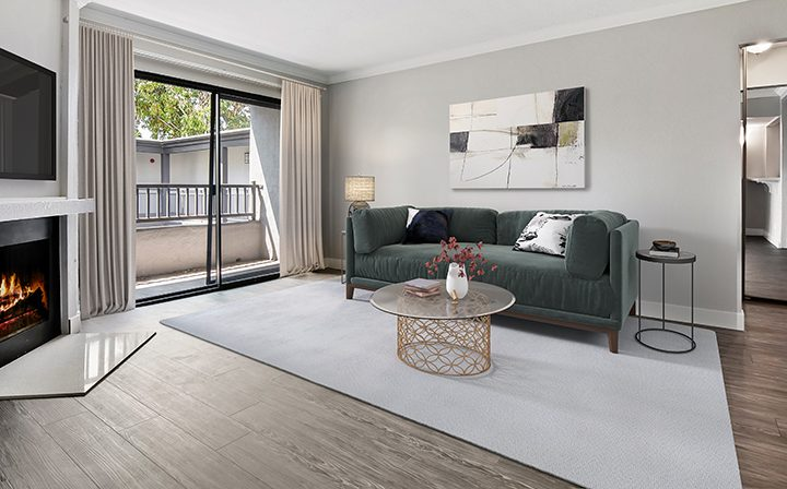 Furnished living room in model unit with balcony exit at Woodland Hills apartments community Alura