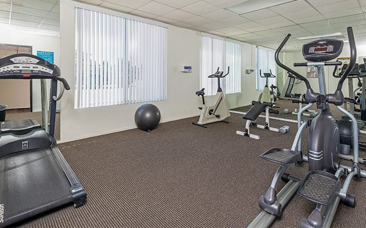 Fitness room with exercise equipment at Amanda Regency, Decron's San Fernando Valley apartments