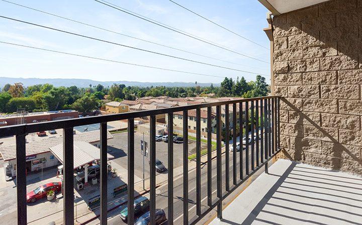 Balcony overlooking buildings and lot at Amanda Regency, Decron's San Fernando Valley apartments