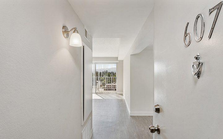 Open apartment door leading to interior at Amanda Regency, Decron's San Fernando Valley apartments