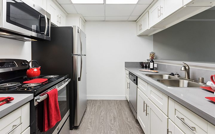 White kitchen with red furnishings at Amanda Regency, Decron's San Fernando Valley apartments