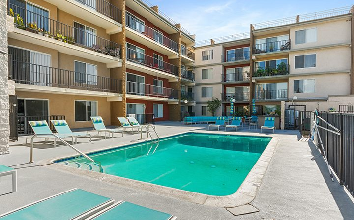 Resort-style pool and chairs at Amanda Regency, Decron's San Fernando Valley apartments