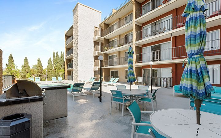 Chairs and tables near pool at Amanda Regency, Decron's San Fernando Valley apartments