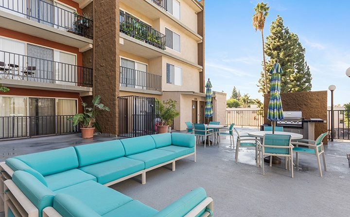 Outdoor lounge seating near pool at Amanda Regency, Decron's San Fernando Valley apartments