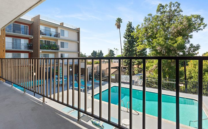 Balcony overlooking resort-style pool at Amanda Regency, Decron's San Fernando Valley apartments
