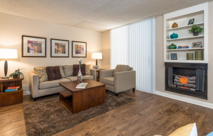 Cozy furnished living room interior with fireplace at Westwood apartments community Ariel Court