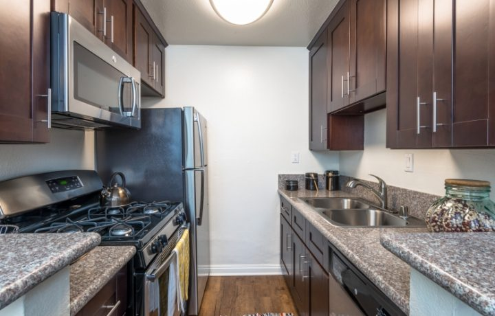 Kitchen with brown cabinets and white walls at Westwood apartments community Ariel Court