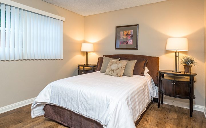 Furnished bedroom with wood floors and white walls at Ariel Court, Westwood apartments near UCLA