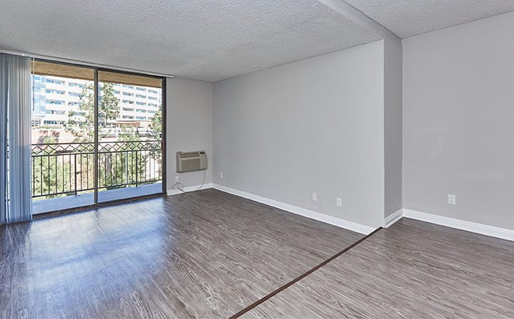Unfurnished apartment living room with balcony exit at Westwood apartments community Ariel Court