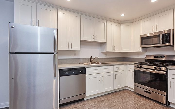 Unfurnished kitchen with white cabinets at Westwood apartments community Ariel Court