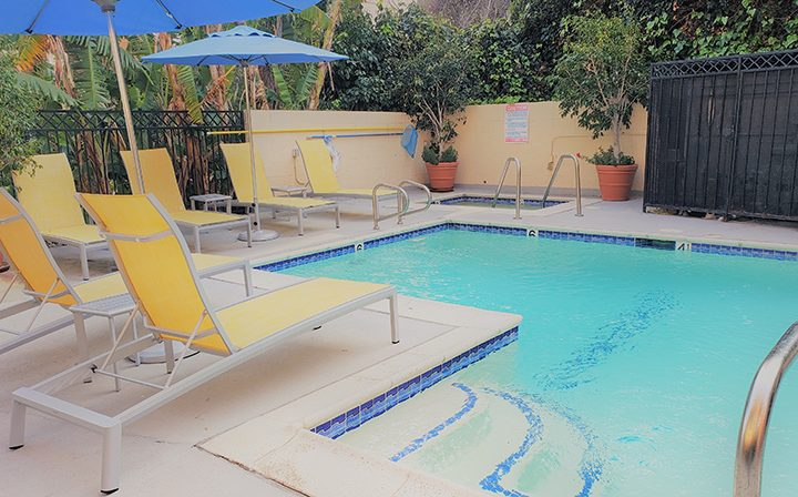 Yellow pool chairs by resort-style pool at Westwood apartments community Ariel Court