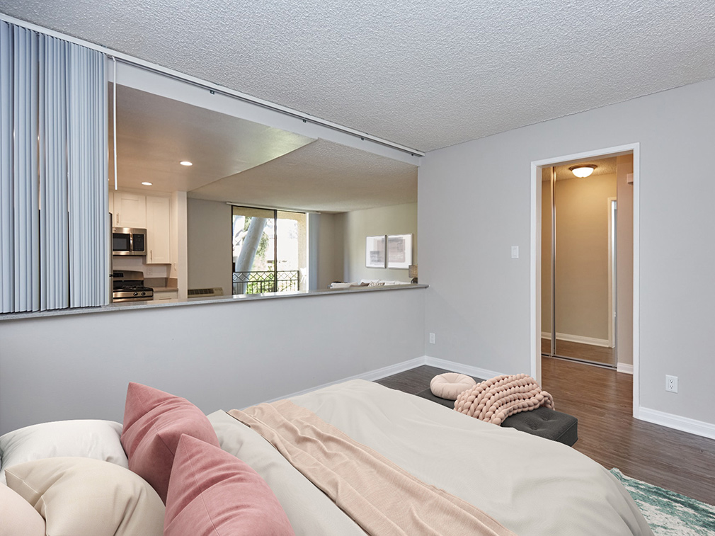 Bedroom with cutaway to living room in model unit at Westwood apartments community Ariel Court