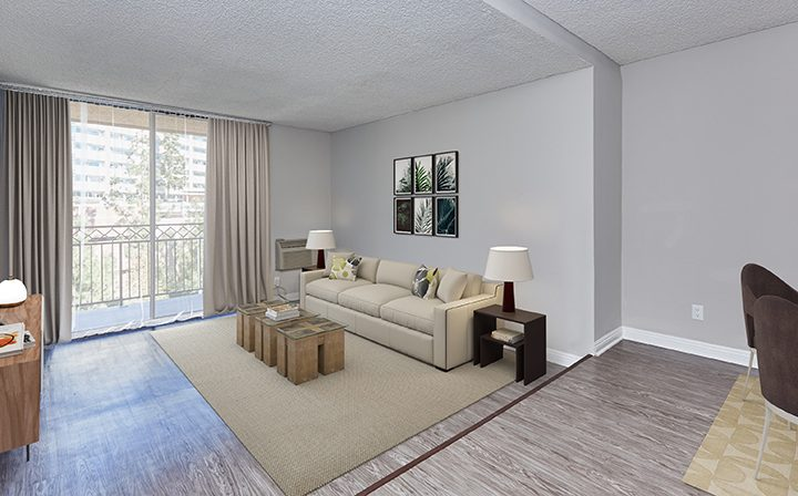 Furnished living room with balcony exit in model unit at Westwood apartments community Ariel Court