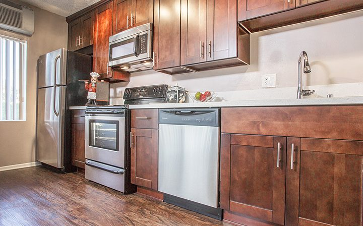 Kitchen with brown cabinets and hardwood floor at the West Hollywood apartments community Ascent