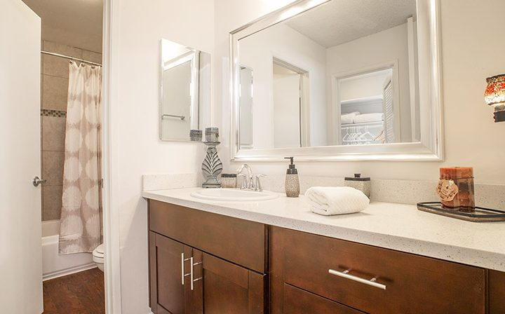 Furnished bathroom with brown cabinets and white walls at West Hollywood apartments community Ascent