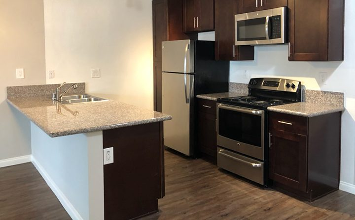 Unfurnished kitchen with brown cabinets at the Pacific Ocean community, apartments in Santa Monica
