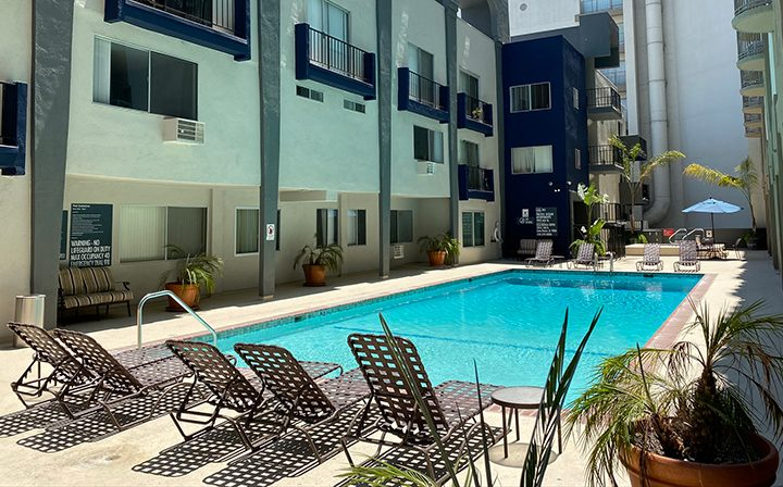 Pool and chairs by the Pacific Ocean community, apartments in Santa Monica with blue accents