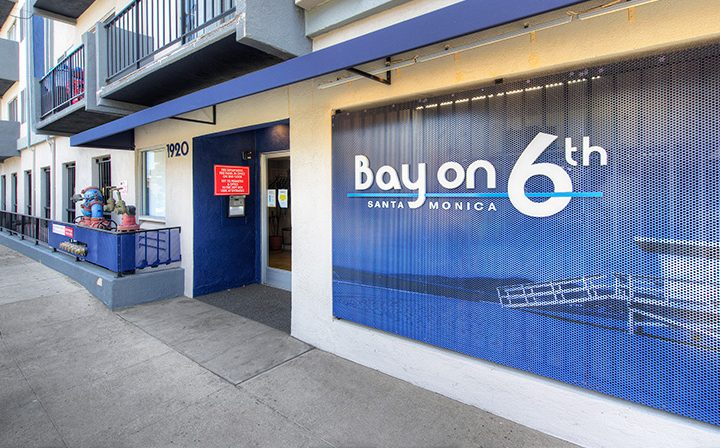 Streetside view of the Bay on 6th entrance, Santa Monica apartments with blue accents
