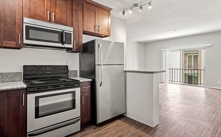 Kitchen and living room with brown accents and floor at a Bay on 6th Santa Monica studio apartment