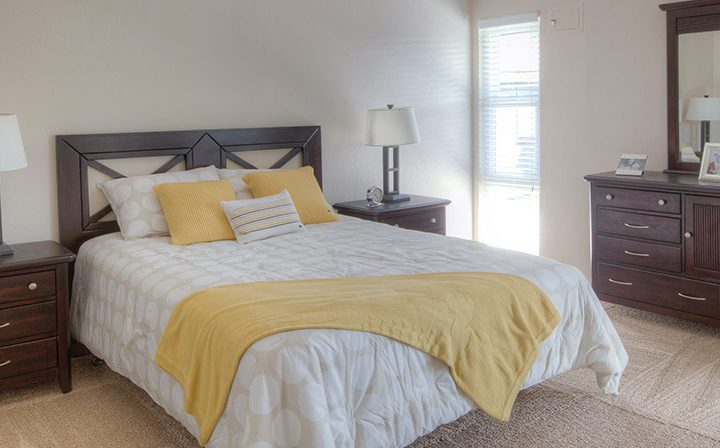 Furnished bedroom with bright window at Mountain View apartments community Highland Gardens