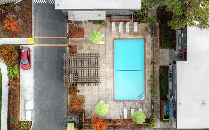 Aerial view of bright blue pool at Mountain View apartments community Highland Gardens