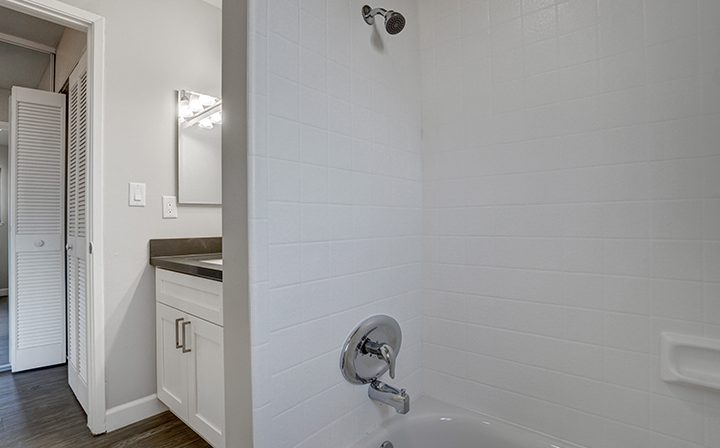 Tiled shower next to sink and vanity mirror at Mountain View apartments community Highland Gardens