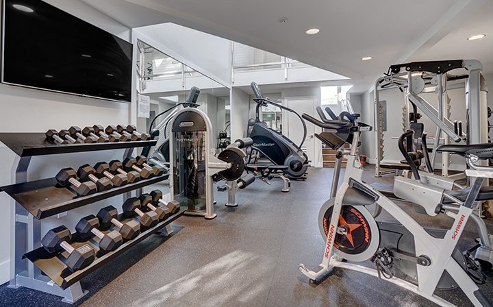 Fitness center with machines and free weights at Mountain View apartment community Highland Gardens
