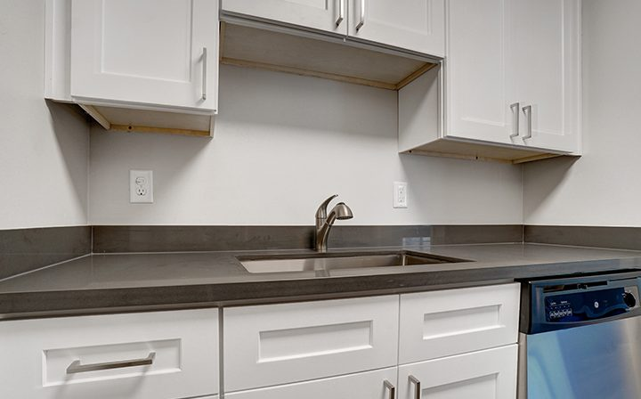 Cabinets over sink and dishwasher in kitchen at Mountain View apartments community Highland Gardens