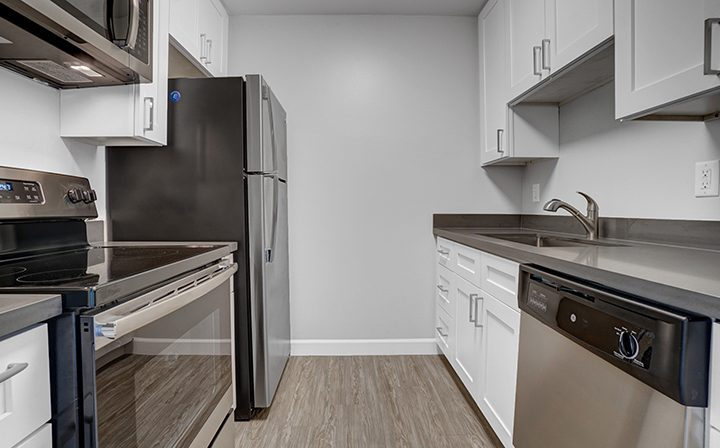 Two-sided kitchen with range and dishwasher at Mountain View apartments community Highland Gardens