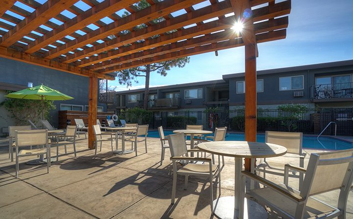 Wood awning over seating next to pool at Mountain View apartments community Highland Gardens