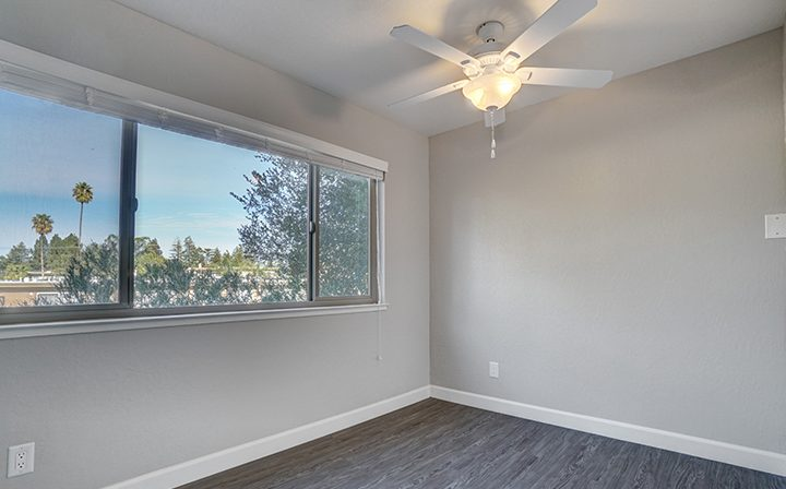 Apartment interior with view of palm trees and city at Mountain View apartments Highland Gardens