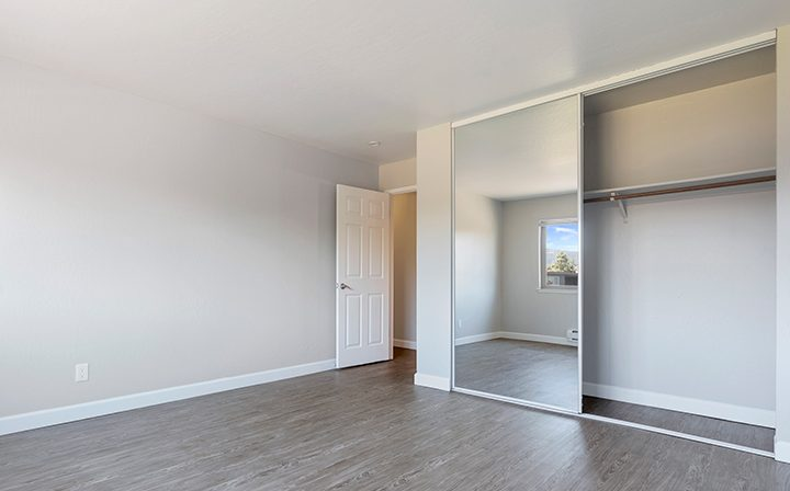 Unfurnished bedroom with mirrored closet at Mountain View apartments community Highland Gardens